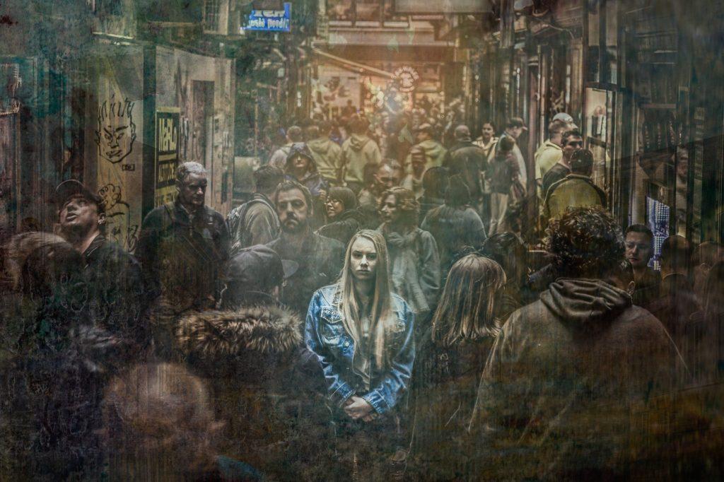 Kuvituskuva, yksi värillinen ihminen keskellä yksiväristen ihmisten joukkoa