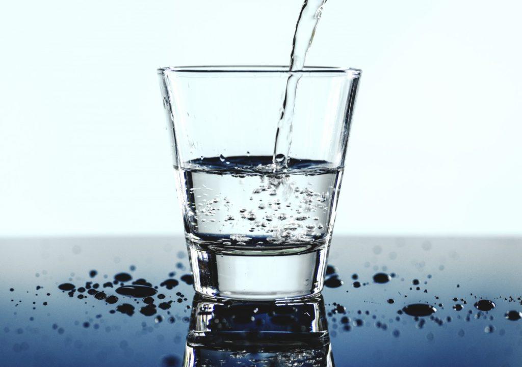 kuvituskuva, jossa kaadetaan vettä vesilasiin