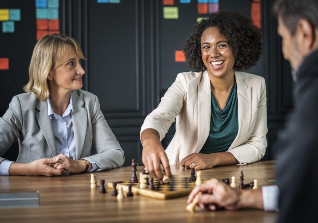 kuvituskuva, jossa kolme ihmistä hymyilee ja pelaa shakkia
