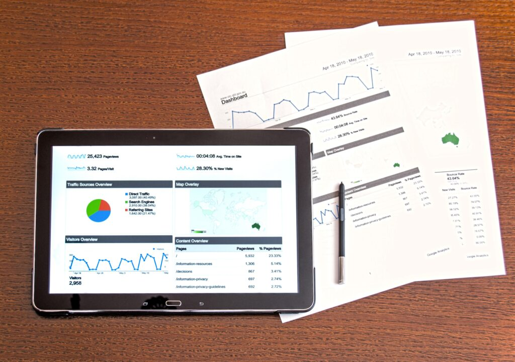 Kuvituskuva, jossa kaavioita ja kuvaajia tablettitietokoneen näytöllä ja paperilla