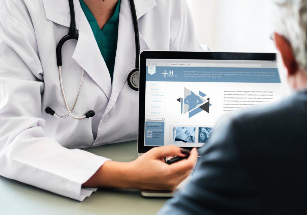 Kuvituskuva, jossa terveydenhoitohenkilö osoittaa tietokoneen ruutua toiselle henkilölle