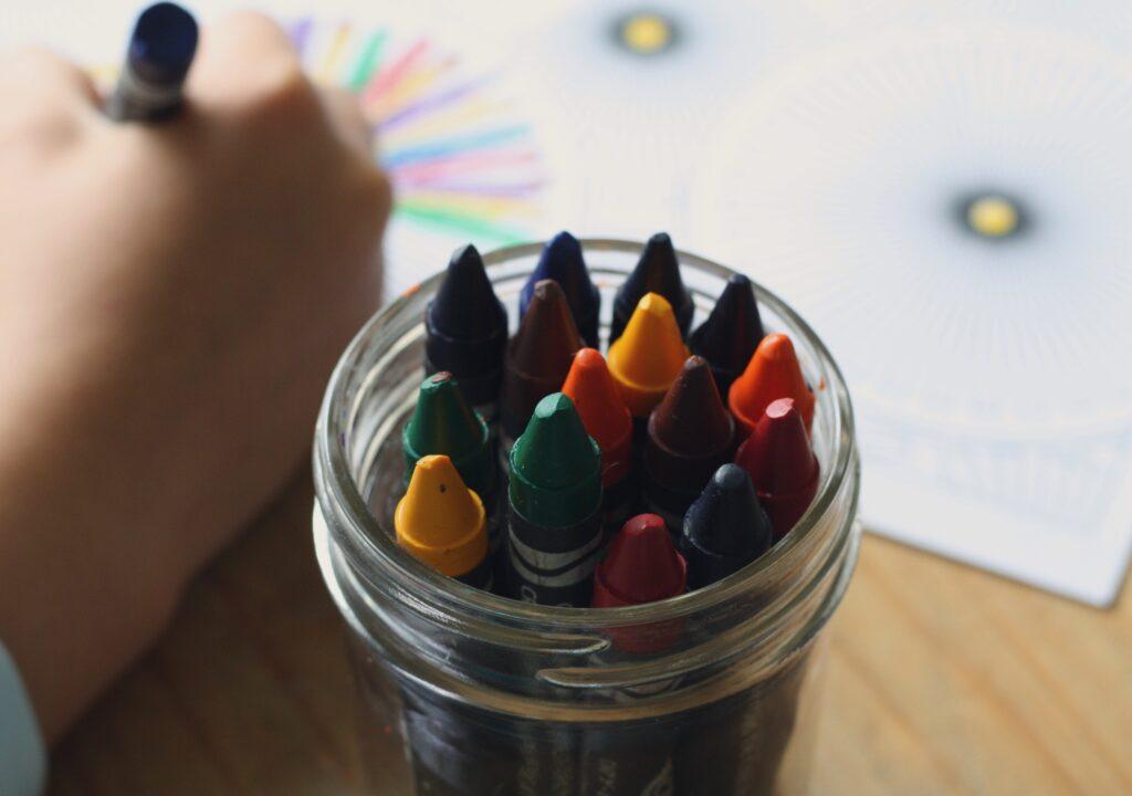 Kuvituskuva, jossa lapsen käsi ja värikyniä