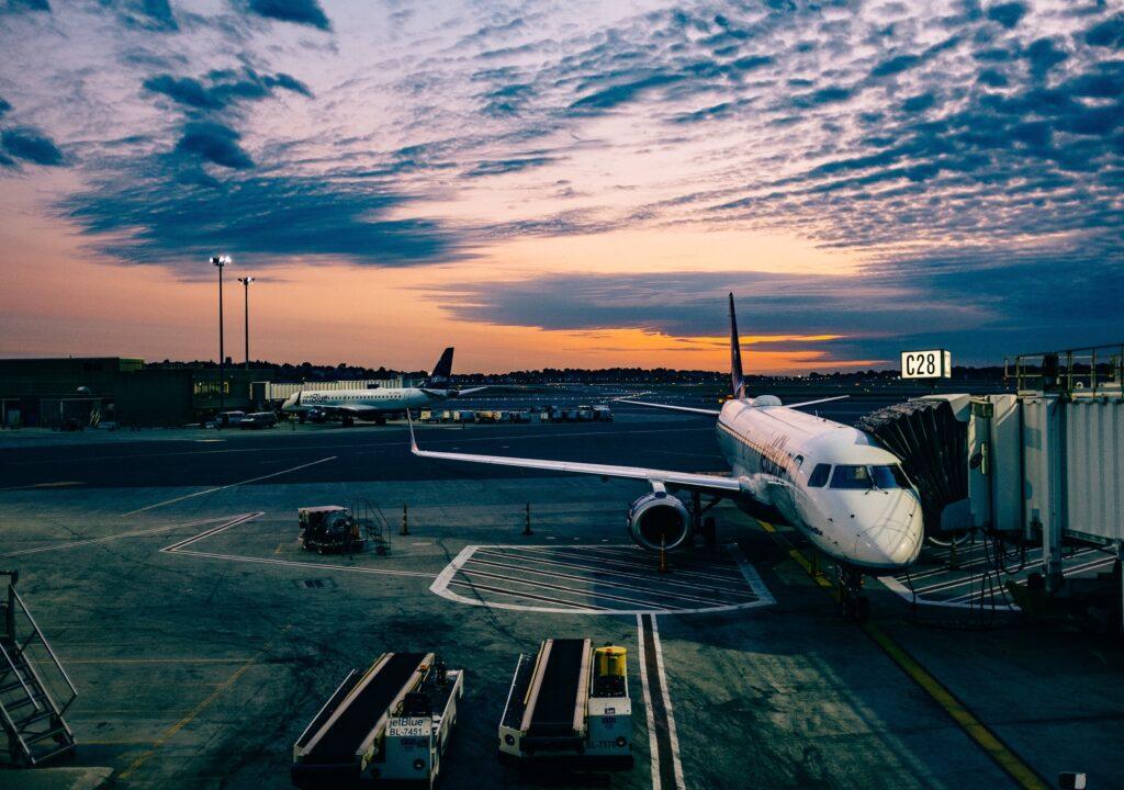 Kuvituskuva, jossa lentokone kentällä auringonlaskun aikaan