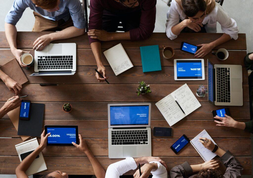 kuvituskuva, jossa ryhmä ihmisiä työskentelee yhdessä kannettavilla tietokoneilla