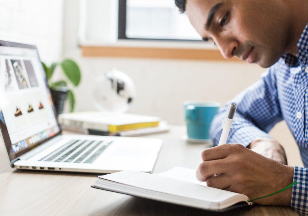kuvituskuva, jossa mies pöydän ääressä kirjoittaa muistikirjaan edessään kannettava tietokone