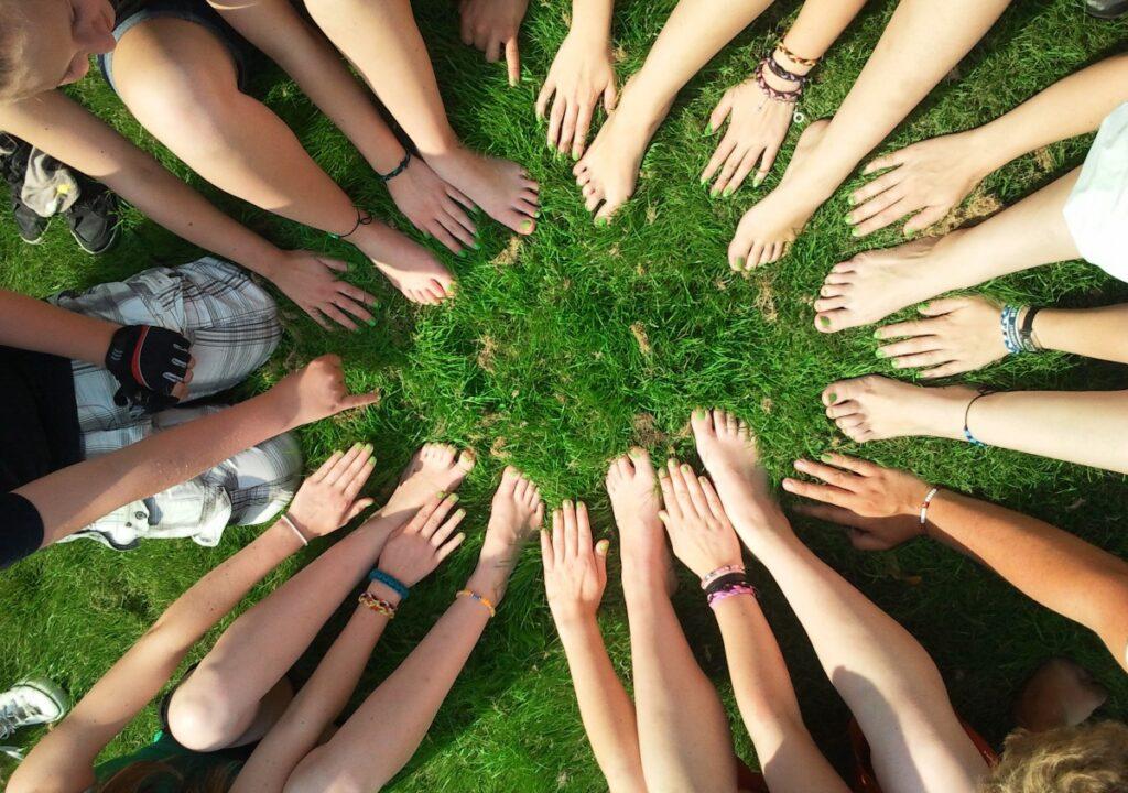 kuvituskuva, jossa ihmisten kädet ja jalat muodostavat ringin nurmikolla