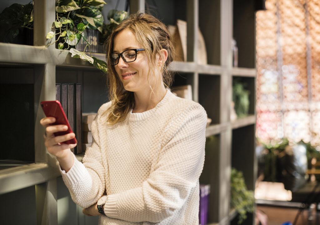 Kuvituskuva naisesta puhelin kädessä