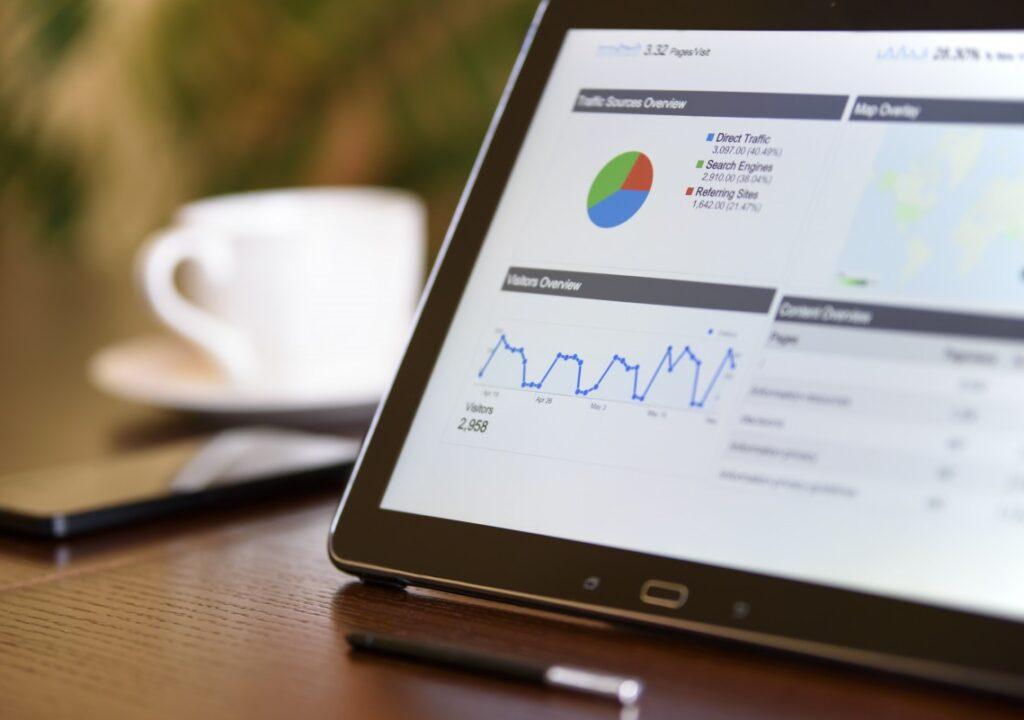 kuvituskuva, jossa pöydällä tabletti jonka ruudulla näkymä webanalytiikkatyökaluista