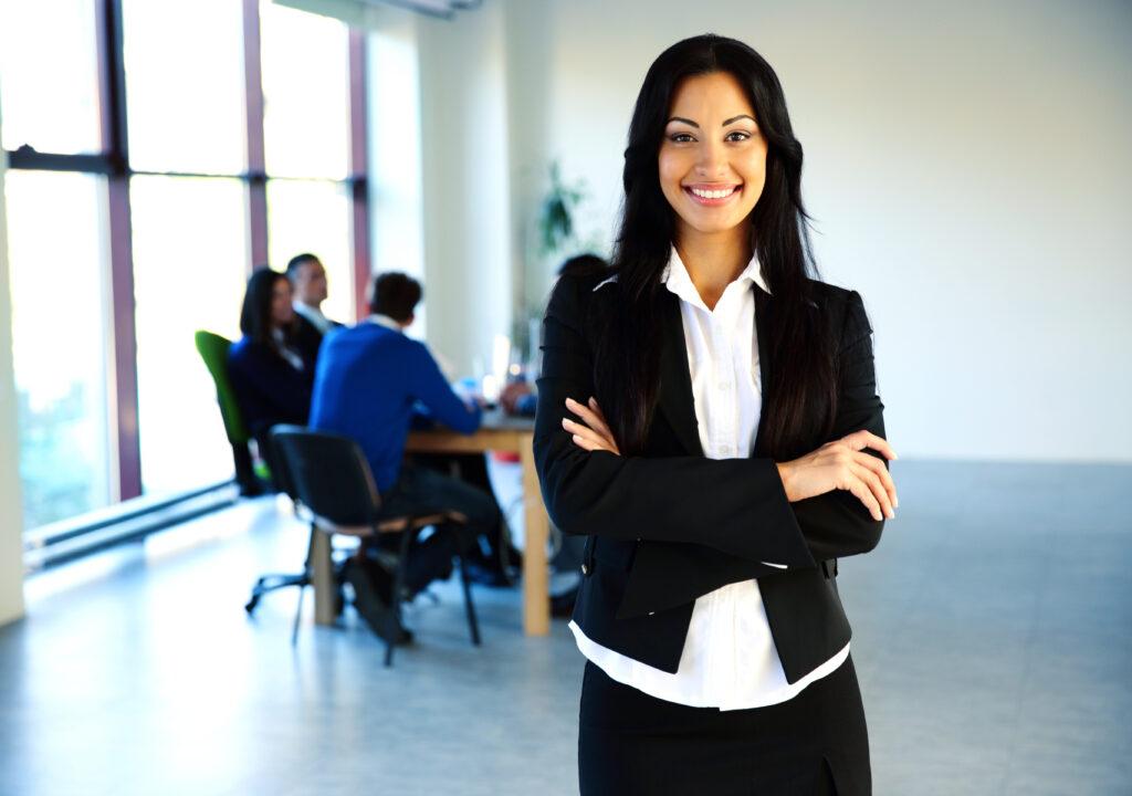 Kuvituskuva, jossa nainen seisoo etualalla ja ryhmä ihmisiä istuu pöydän ääressä taka-alalla