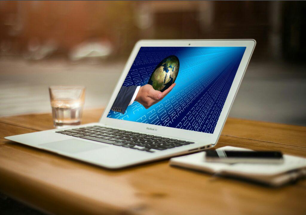 Kuvituskuva, jossa tietokoneen näytöllä näkyy maapallo ihmisen käden päällä