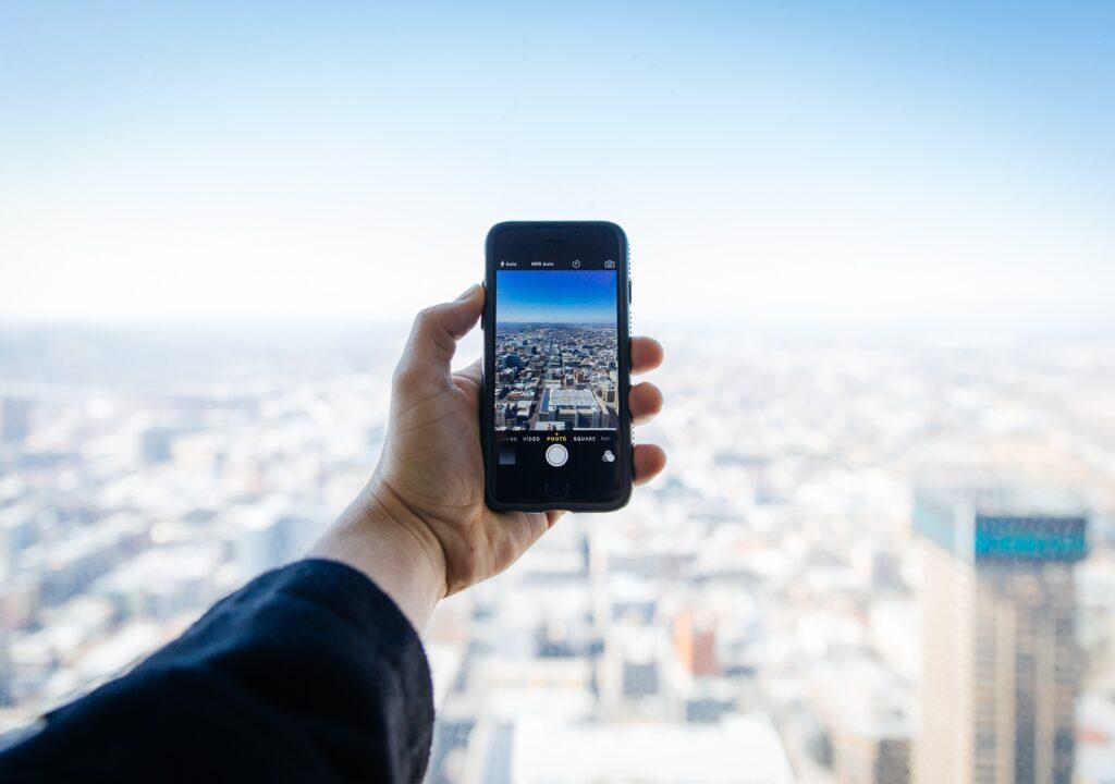 Kuvituskuva, jossa puhelimen kameralla katsotaan kaupunkimaisemaa