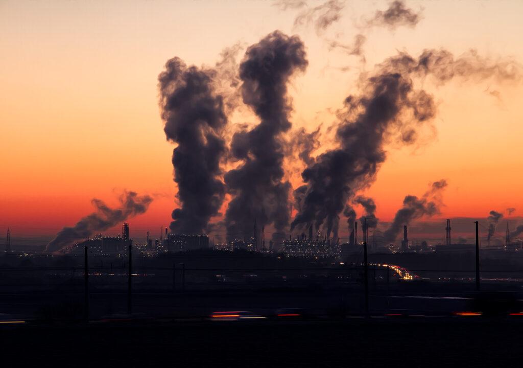 kuvituskuva, jossa savuavia tai höyryäviä tehtaanpiippuja