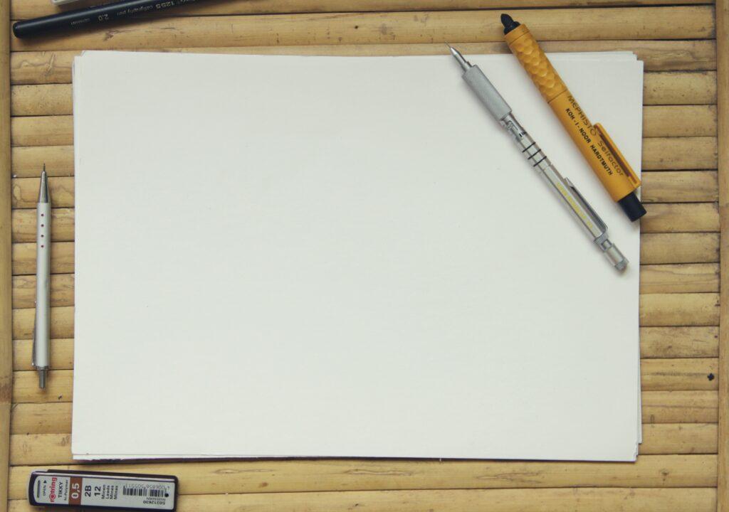 Kuvituskuva, jossa tyhjä paperi ja kyniä puisella alustalla