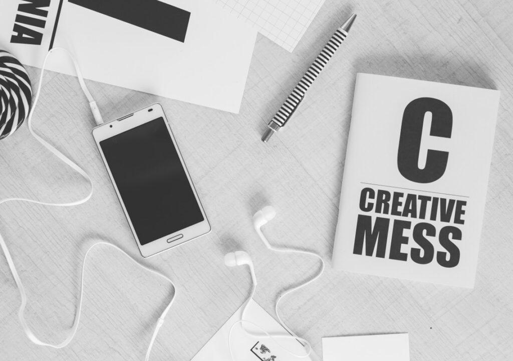 kuvituskuva, jossa pöydällä kynä, matkapuhelin ja lehtiö jossa teksti Creative mess.