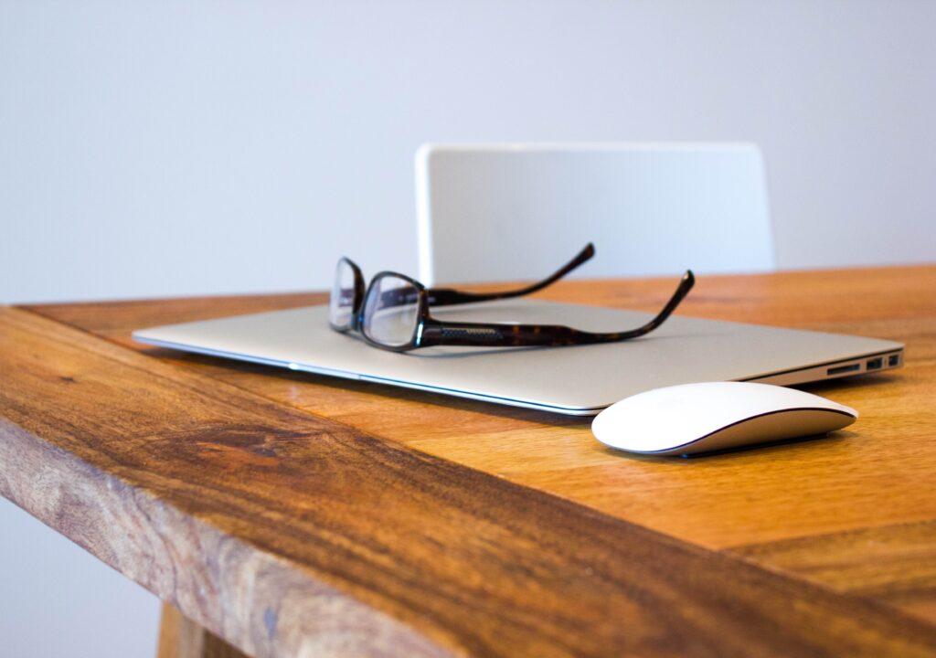 Kuvituskuva, jossa kannettava tietokone, hiiri ja silmälasit puupöydällä