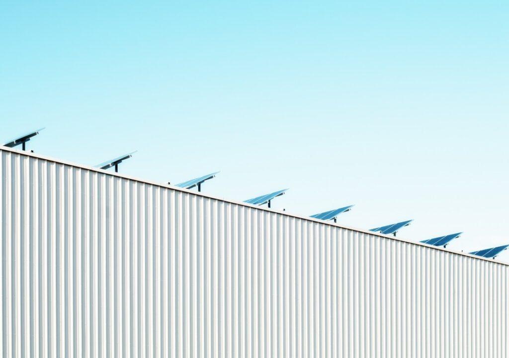 kuvituskuva, jossa aurinkopaneeleja rakennuksen katolla
