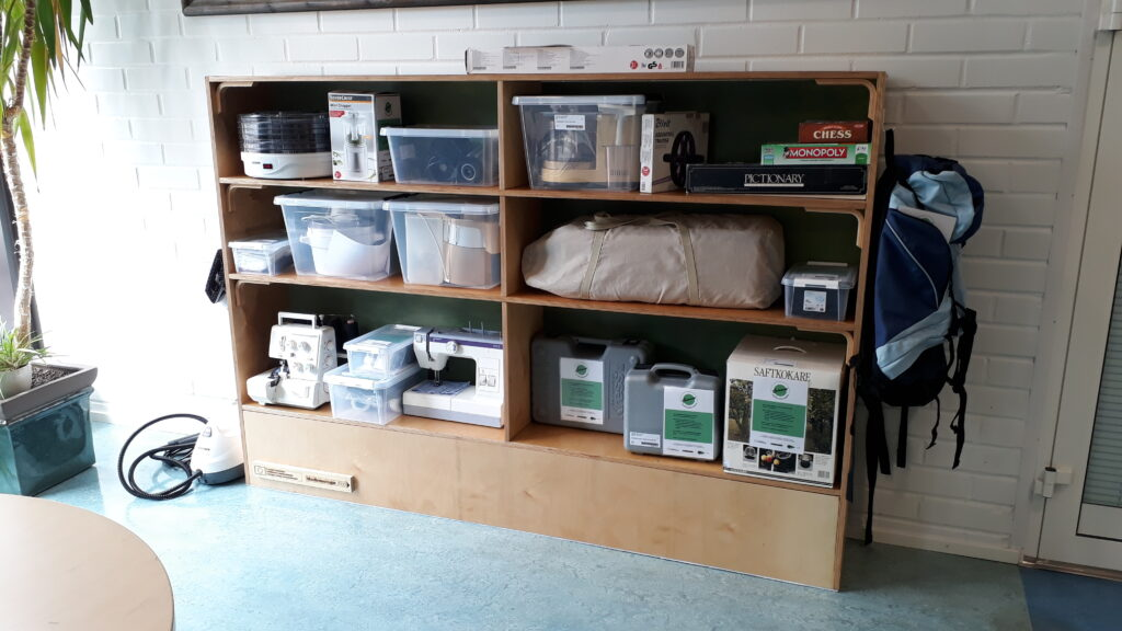 Shelf containing materials available for lending, like kitchen appliances, power tools and a sewing machine.