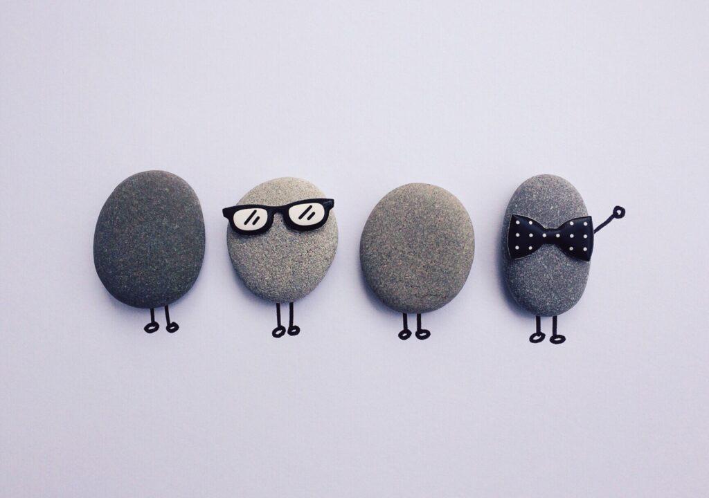 Kuvituskuva, jossa on neljä kivihahmoa, joista yhdellä silmälasit ja toisella rusetti.