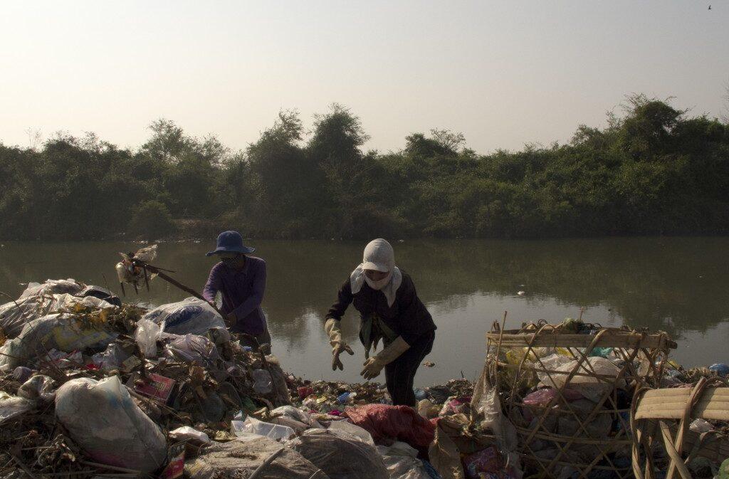Valokuvassa taustalla joki ja etualalla mies ja nainen, jotka tutkivat joenpenkalla olevaa jätekasaa.