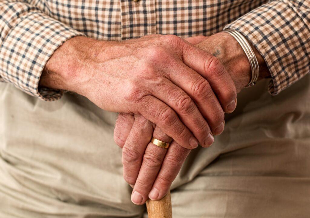 Kuvassa vanhan miehen kädet ja kävelykeppi.