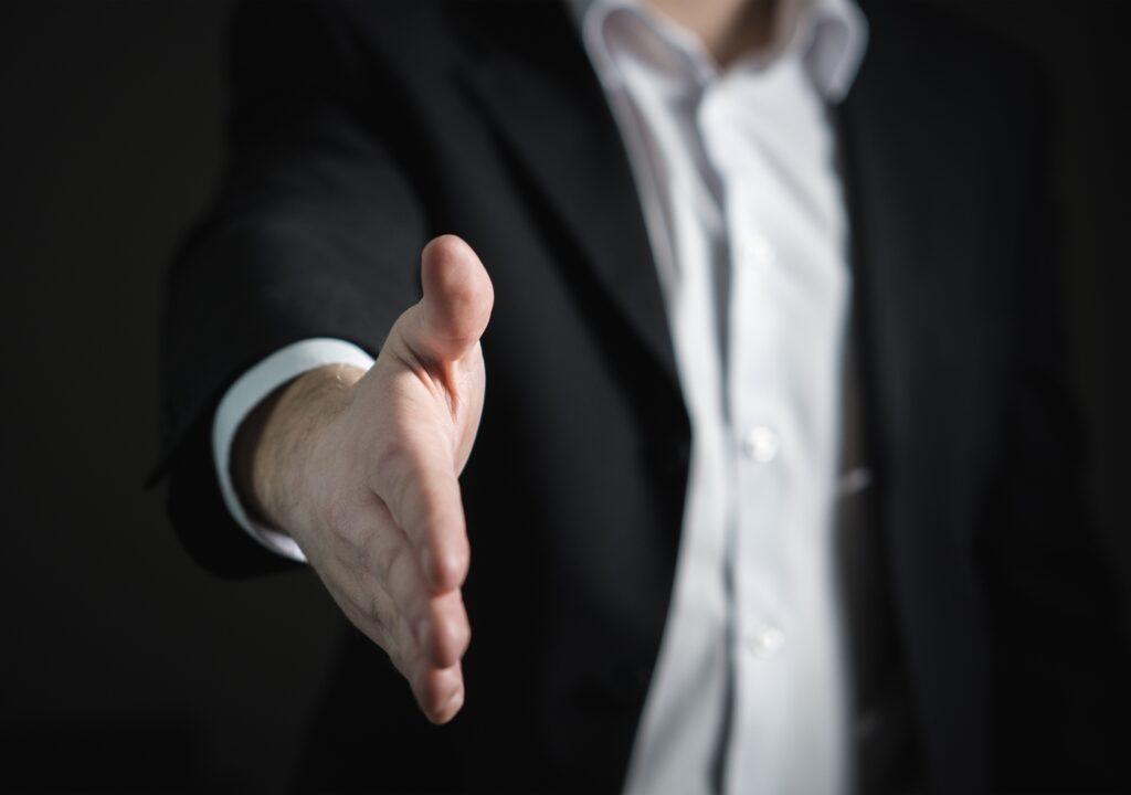 Kuvassa mies, jolla on puvuntakkiin pukeutunut mies ojentaa oikean kätensä.