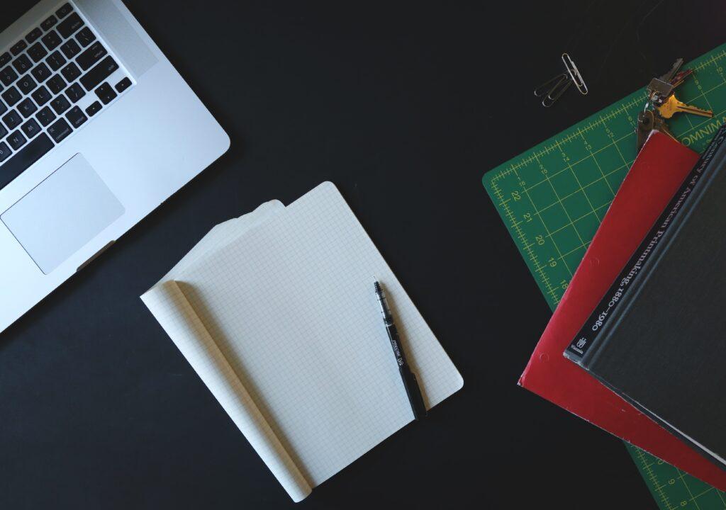 Kuvassa laptop-tietokone, vihkoja, kynä ja kirjoja.