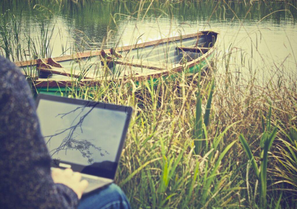 kuvituskuvana valokuva, jossa henkilö istuu rannalla kannettava tietokone sylissään. Taustalla näkyy vettä ja soutuvene.