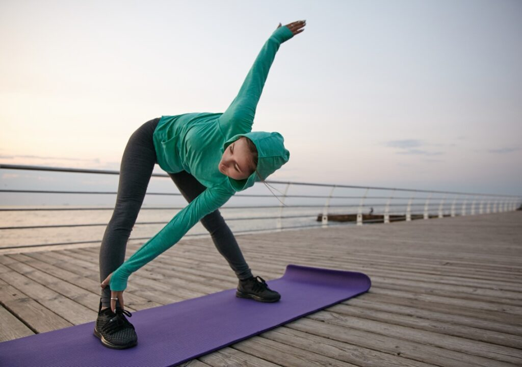 A young woman doing yoga on a pier, lake in the background.