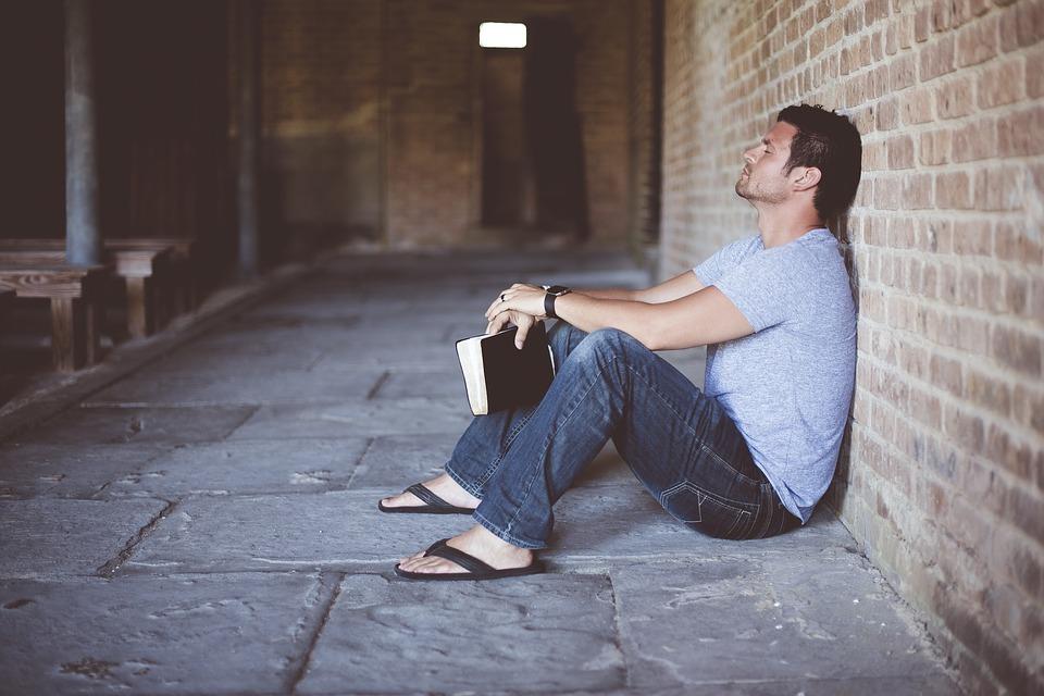 kuvituskuvana on valokuva, jossa yksinäinen mies nojaa istualteen tiiliseinään ja pitää kädessään kirjaa