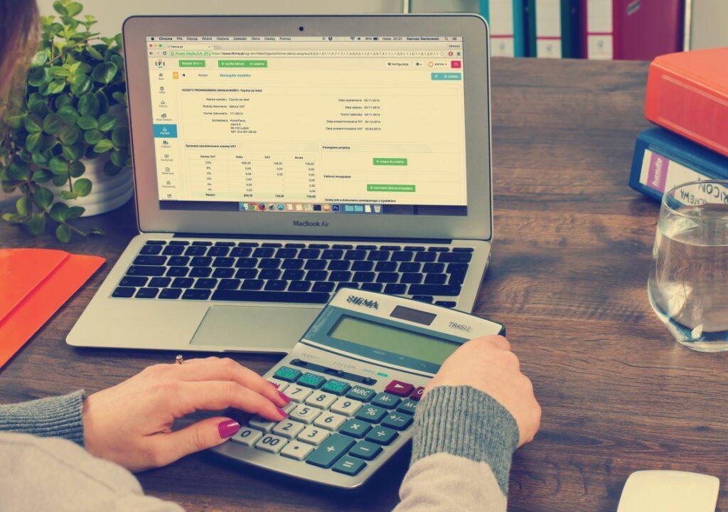 kuvituskuva, jossa työpöydällä naisen edessä on kannettava tietokone ja kädessään laskin.