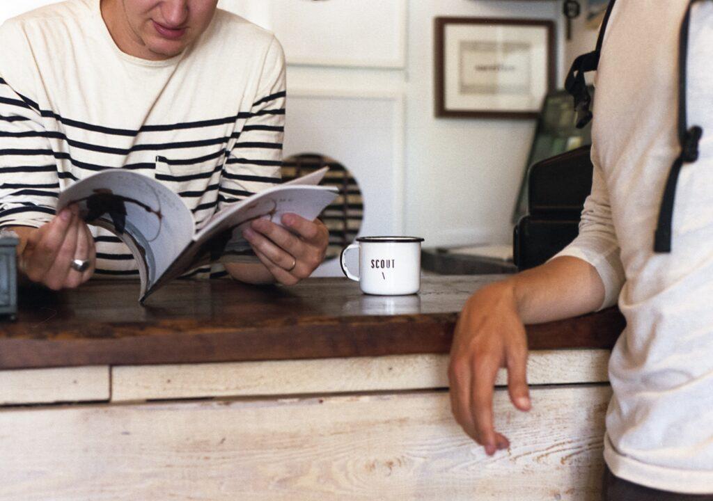 Kuvituskuva, jossa kaksi henkilöä keskustelee seisten pöydän ääressä