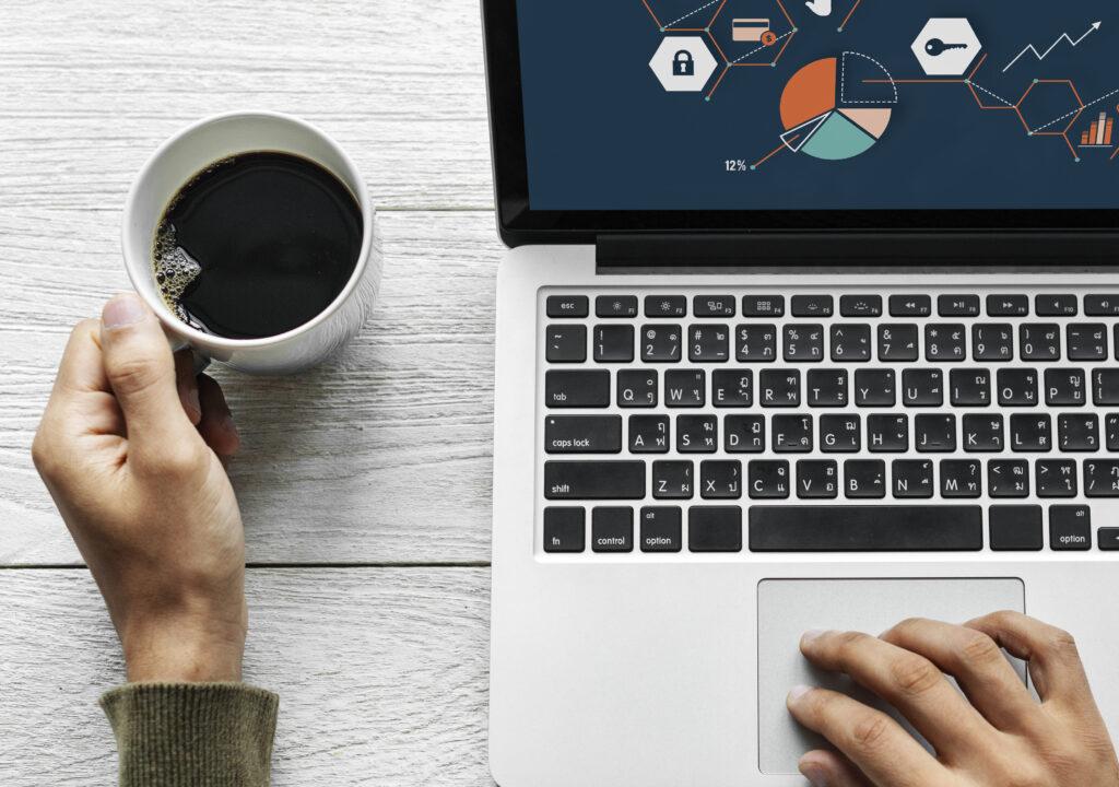 Kuvassa on kannettu tietokone, jonka ruudulla näkyy erilaisia kuvioita, jotak on liitetty verkostomaisesti toisiinsa. Koneen käyttäjästä näkyvät hänen kätensä. Toinen käsi pitää kiinni täydestä kahvikupista.