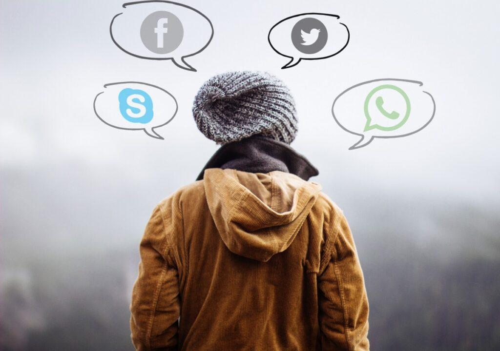 valokuvassa selin kameraan päin oleva ihminen, jonka pään ympärille on lisätty puhekuplissa sosiaalisen median kanavien logoja.