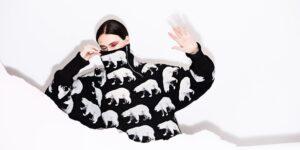 valokuvassa nainen, jolla päällään musta takki jossa valkoisia jääkarhuja