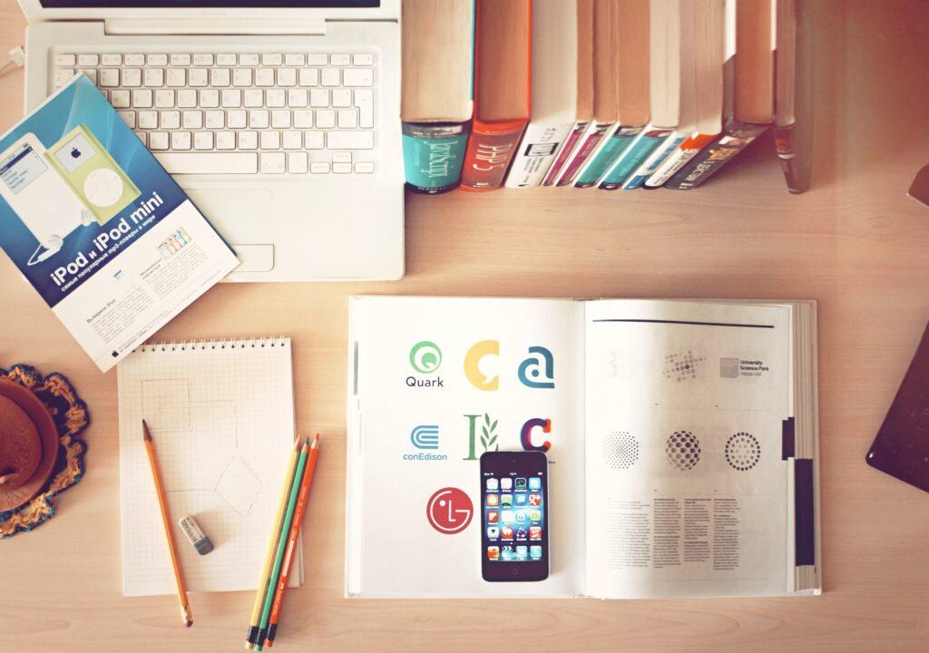 kuvituskuva, jossa pöydällä tietokone, kirja, kännykkä, vihko ja kynä