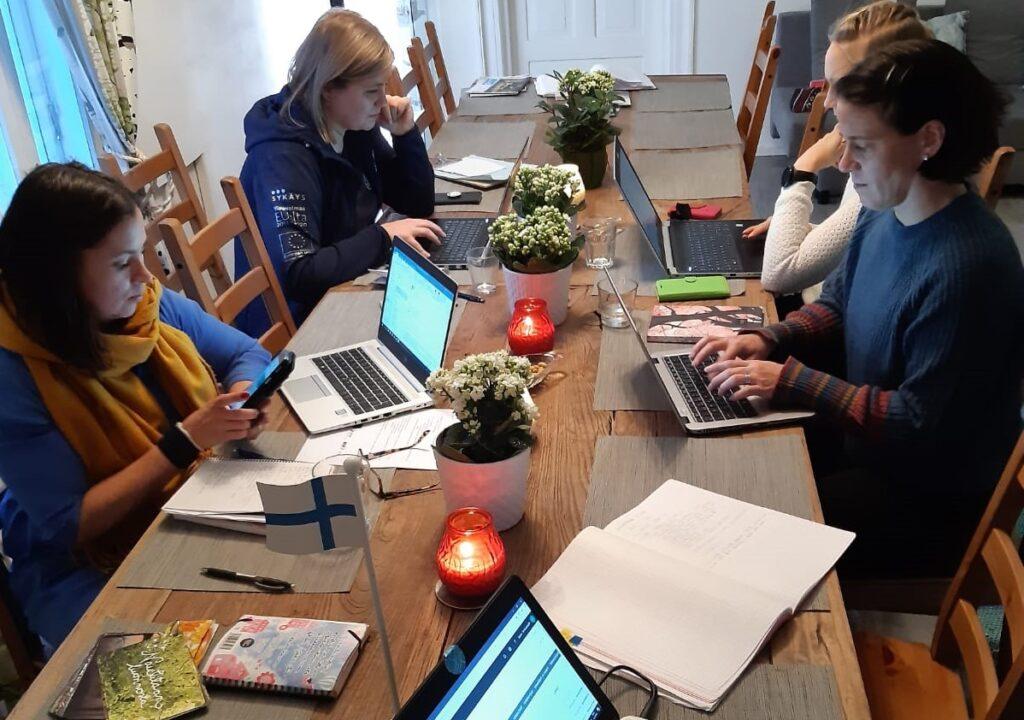 Kuva projektiryhmän neljästä jäsenestä työskentelemässä pödän ääressä kannettavilla tietokoneilla
