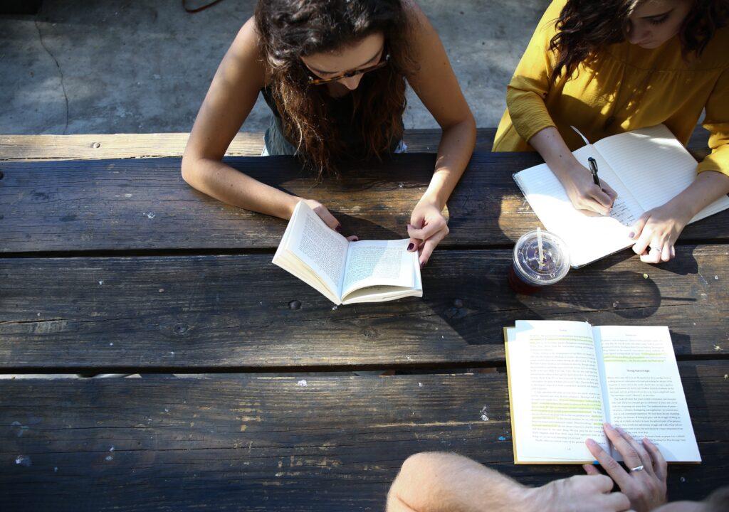 Kuvituskuva jossa naisia pöydän ääressä kirjat käsissään