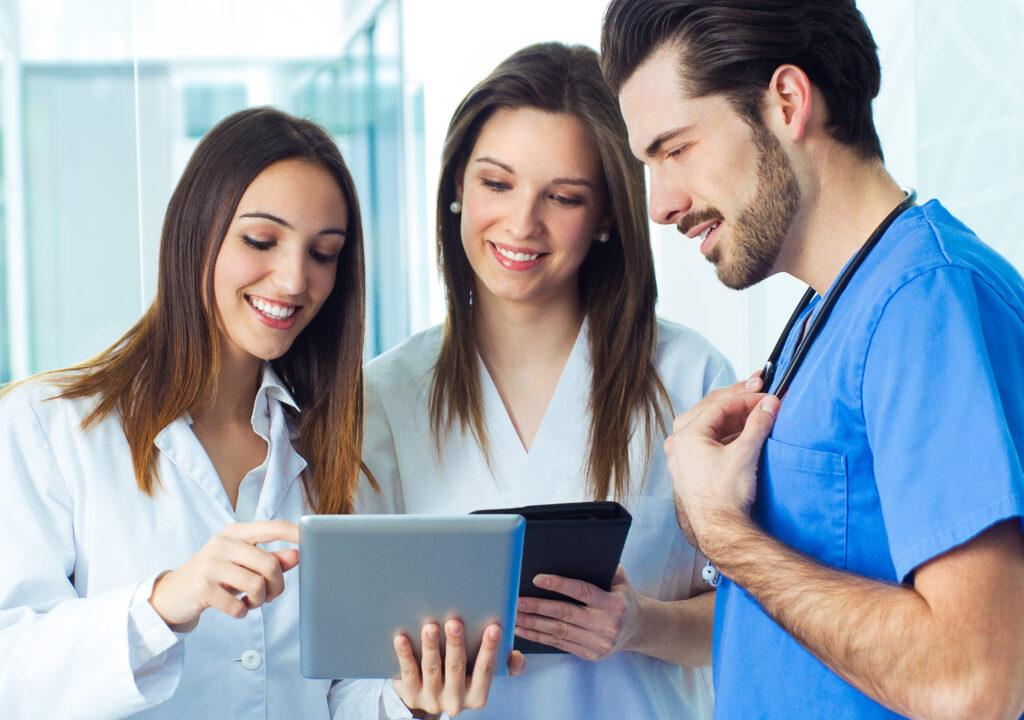 Kuvituskuva, jossa on hoitohenkilökuntaa, eli kaksi naista ja yksi mies. Naisilla on padit käsissä ja he katsovat tietoja niiden näytöiltä.