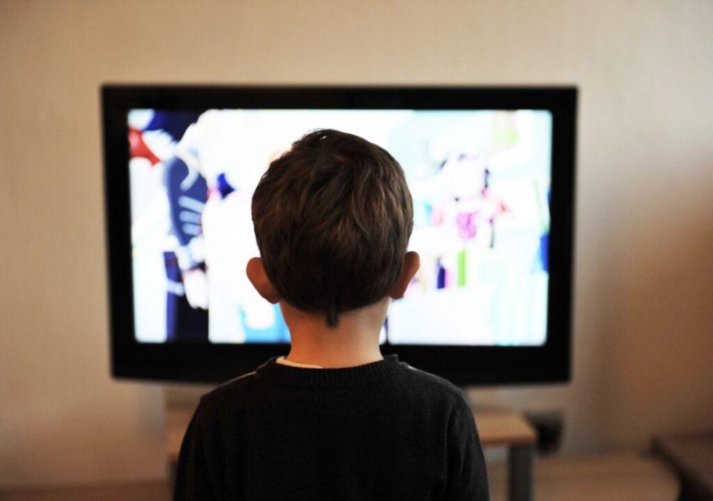Kuvituskuvassa lapsi on selin kameraan päin ja katsoo televisiota.