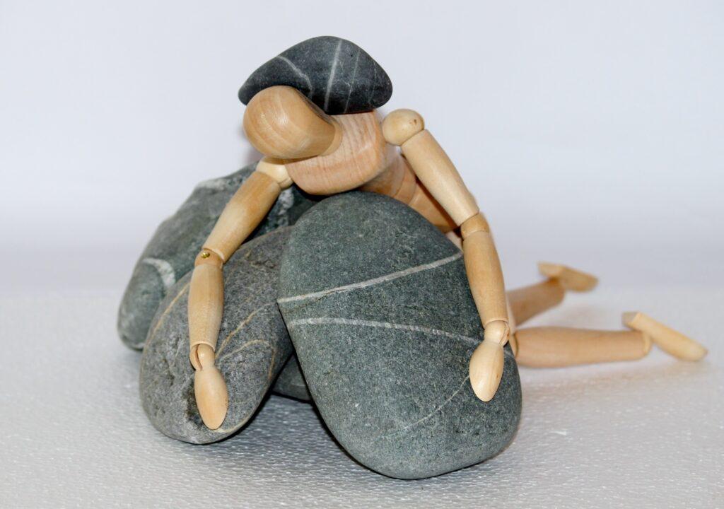 Kuvituskuva, jossa ihmistä esittävä lelu on jäänyt jumiin isojen kivien keskelle.
