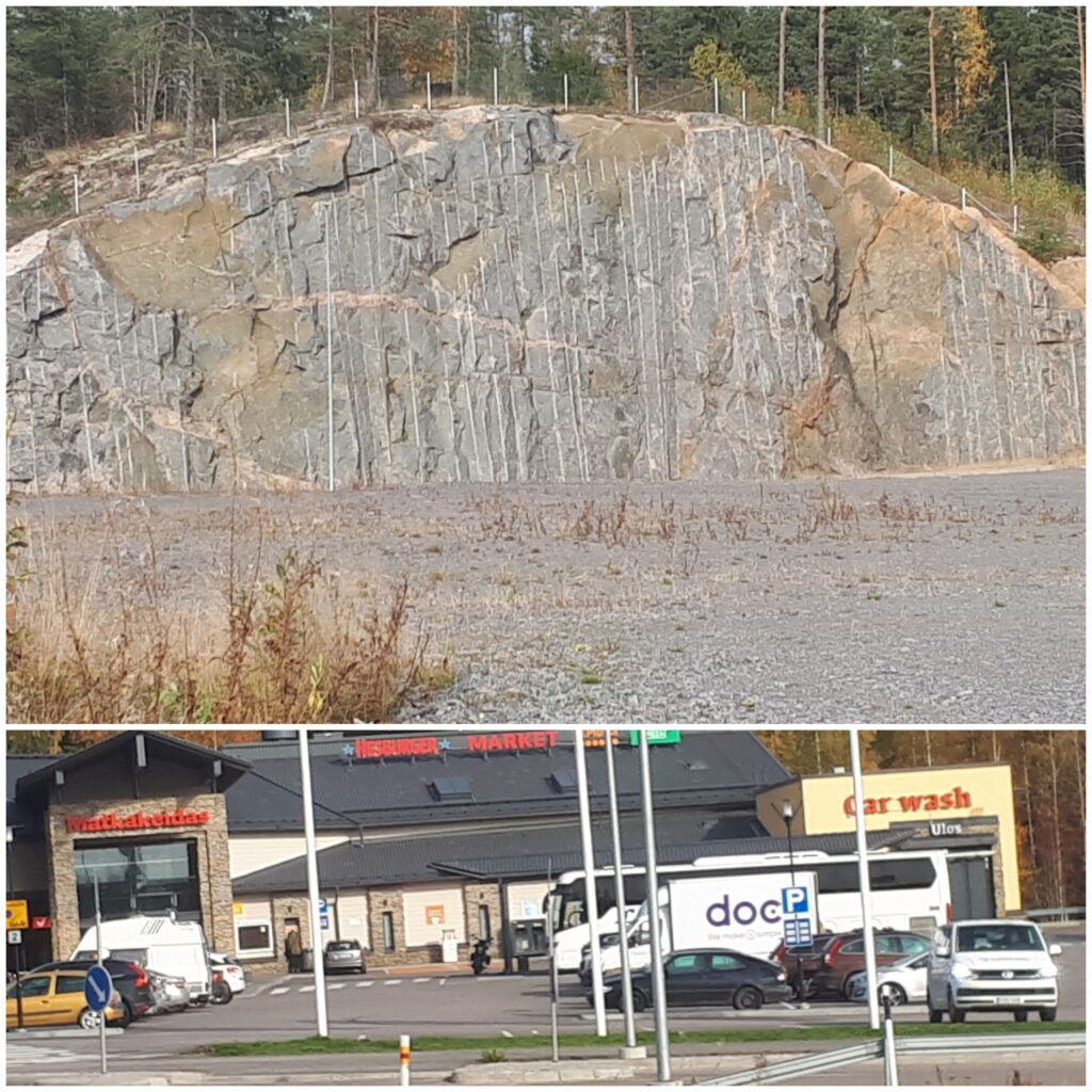 Kuvan yläosassa on iso kallio ja alaosassa kauppa, jonka edessä on parkkipaikka ja siellä autoja parkissa.