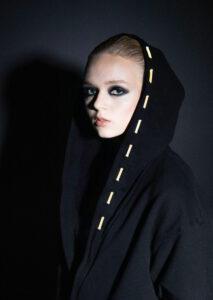 valokuvassa nainen, jolla päällään musta hupullinen takki, hupun reunaa kiertää led-nauha.