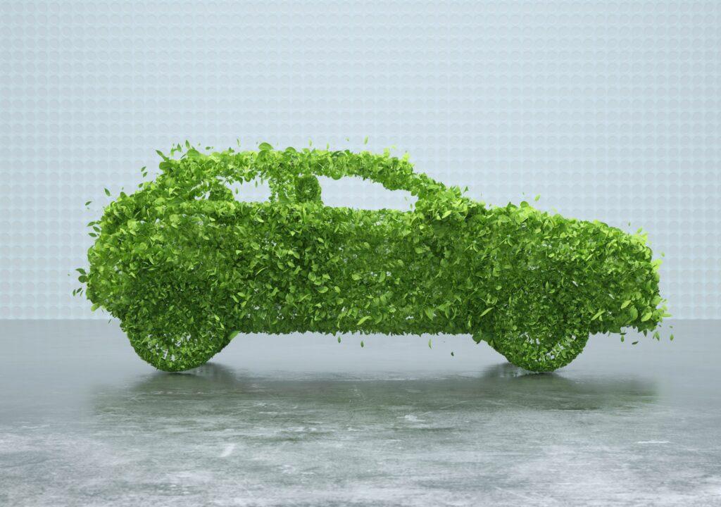 Kuvituskuva, jossa on vihreistä puunlehdistä muotoiltu auton kuva.