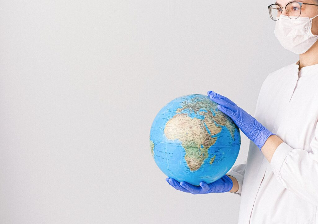 artikkelikuvassa kasvomaskiin ja sinisiin hanskoihin pukeutunut nainen pitelee käsissään maapalloa.