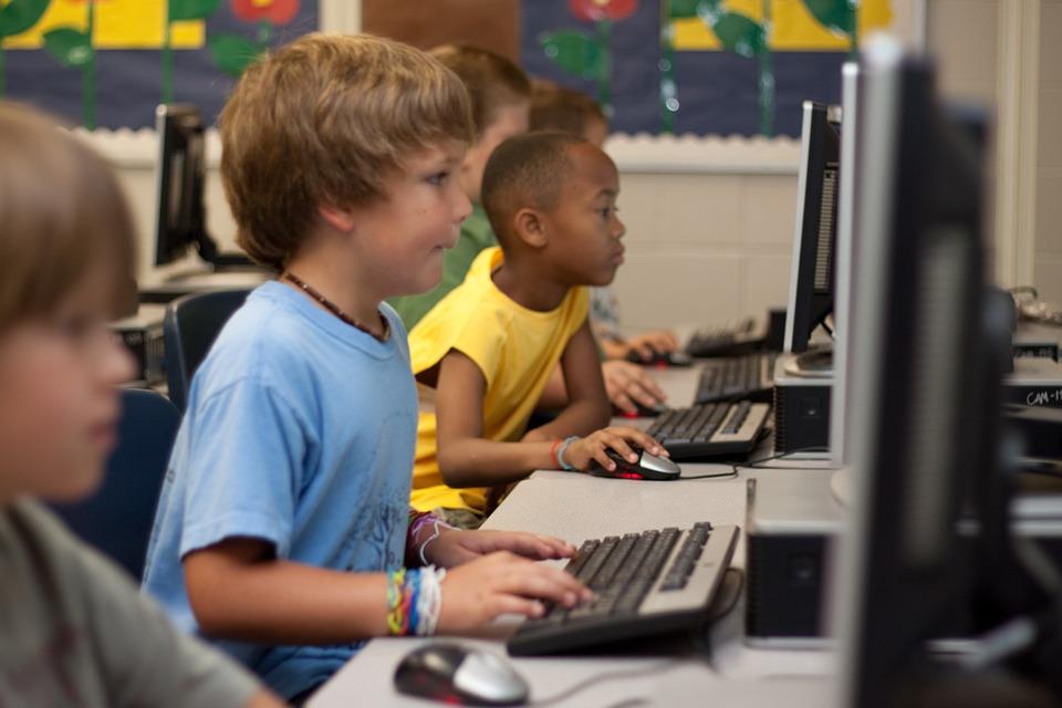 Artikkelikuvana valokuva, jossa lapsia tietokoneiden äärellä.