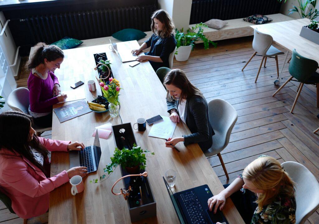 Kuvituskuva, jossa on ihmisiä työskentelemässä tietokoneillaan pitkän pöydän molemmin puolin.