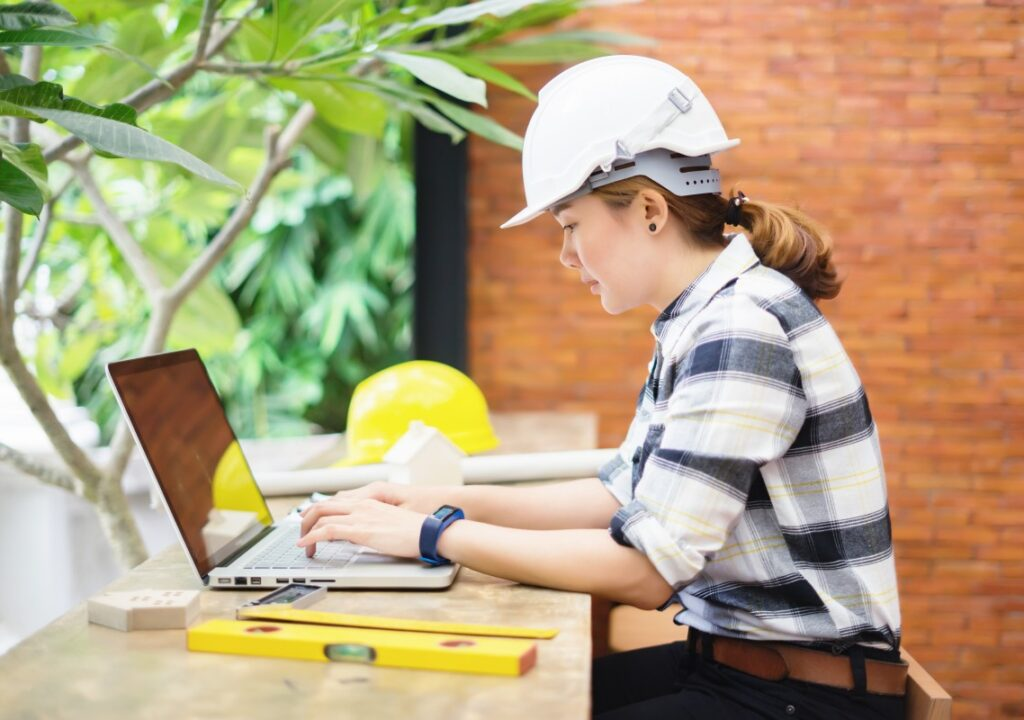 Tietokoneella työskentelevä nainen, jolla päällään ruutupaita ja valkoinen turvakypärä.