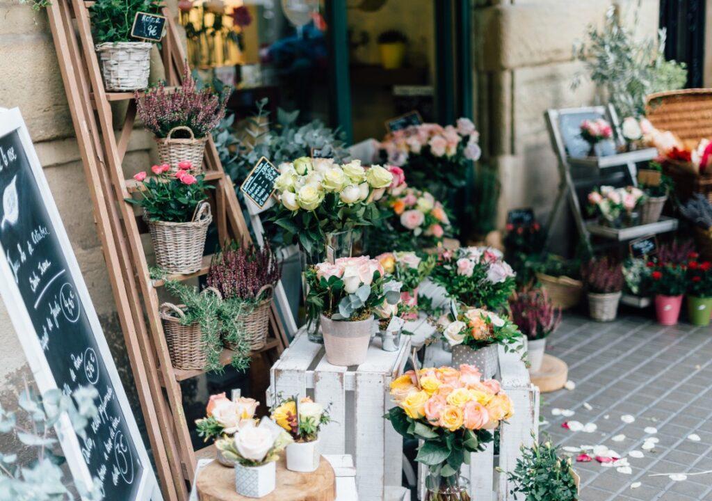 Valokuva kukkakaupan edustalta, jossa kadulle on aseteltu erilaisia kukkakimppuja ja kukka-asetelmia.