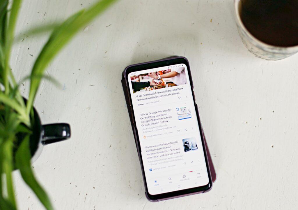 Kuvituskuva, jossa on kännykkä pöydälle. Kännykän näytöllä näkyy linkkejä verkkoartikkeleihin. Kuvassa näkyy myös osa viherkasvia ja kahvikuppia.