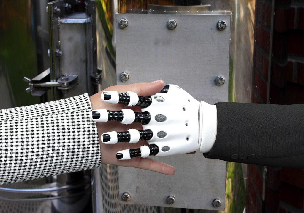 Kuvituskuva, jossa ihmisen ja robotin käsi kättelevät.
